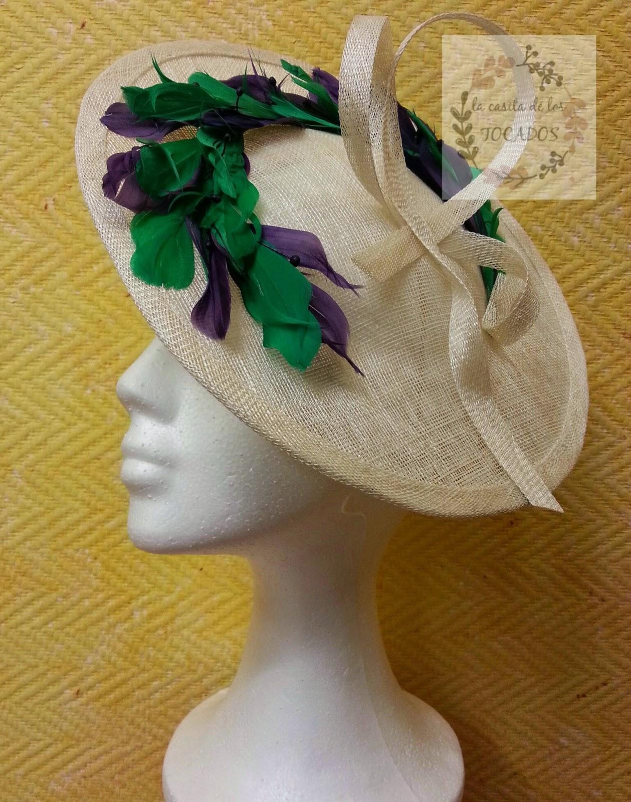 tocado para boda con base en crudo y adorno de plumas combinadas en verde y morado o berenjena