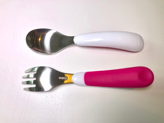 A fork and a spoon with metal ends and plastic handles. The top half is white and the lower half is pink silicone