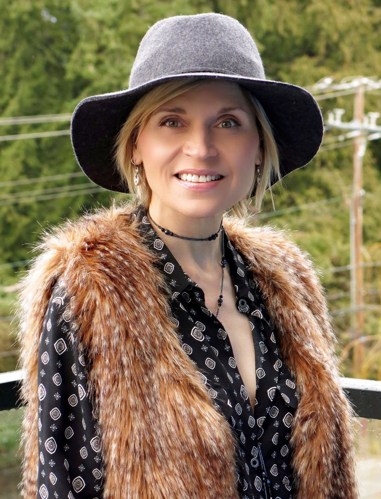 black patterned shirt, long faux-fur vest, and floppy hat