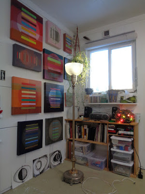 "One corner of the garage studio, showing a few of the ""Sound"" paintings and shelving with books and printmaking tools and materials.  Also the Creative Brain, my studio mascot."