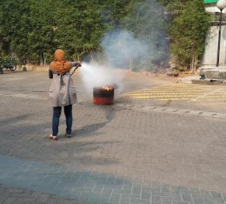 seorang ibu memadamkan api menggunakan tabung pemadam