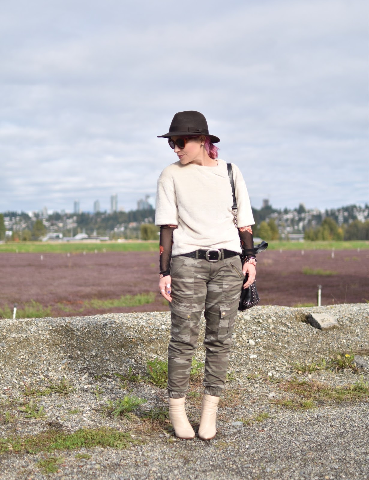 Monika Faulkner outfit inspiration - mesh floral and ivory faux-fur tops, camouflage trousers, ivory booties, felt fedora, cat-eye sunglasses