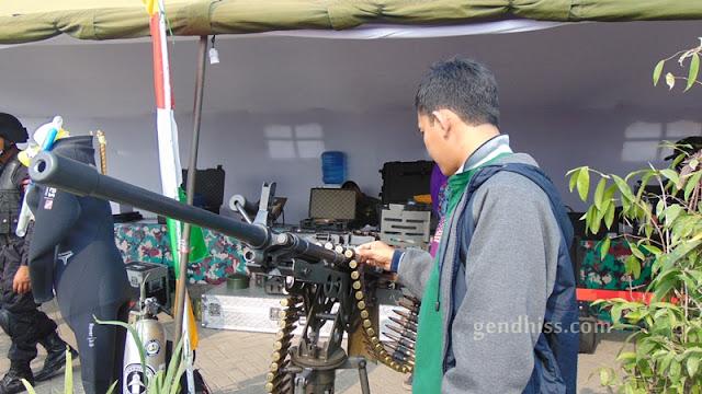 Suami sedang menilik peluru di pameran TNI