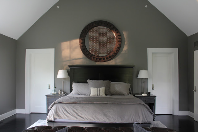 White closet doors flanking bed in lofty farmhouse bedroom with grey walls. Modern Industrial Farmhouse Bedroom Design {2nd Floor Tour}. #modernfarmhouse #bedroom #industrialfarmhouse #greywalls #luxuriousfarmhouse #benjaminmooreplatinum #benjaminmoorestoningtongray