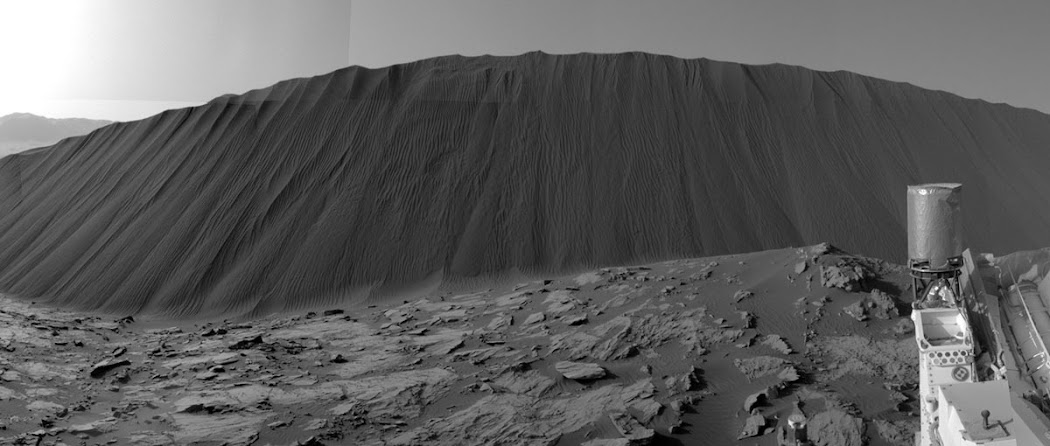 Khung cảnh này từ đôi mắt của tàu tự hành Curiosity được chụp khi nó đứng bên dưới Đồi cát Namib cao 4 mét. Khu vực này là một phần của Đồi cát Dunes lớn hơn, tạo thành một dải cát tối màu chạy dọc theo sườn phía tây bắc của Núi Sharp. Hình ảnh này cũng được ghép lại từ những hình ảnh nhỏ hơn để tạo ra ảnh toàn cảnh góc rộng, được chụp vào ngày 17 tháng 12 năm 2015, nhằm sol 1196. Hình ảnh: JPL-Caltech/MSSS/NASA.