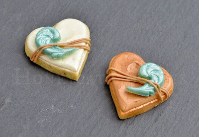 Crushed royal icing effect on mini heart cookies with marzipan raised elements and piped 'string'.