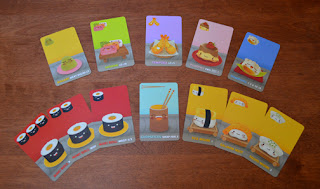 A display of the various cards available in Sushi Go. In the top row is Wasabi, Sashimi, Tempura, Pudding, and Dumplings. The bottom row has three Maki Roll cards, which are identical except one has a single Maki Roll icon, another has two icons, and the last has three. Next to these is the Chopsticks, followed by the three Nigiri cards: Egg, Salmon, and Squid. All of these cards are a different colour, except all the Maki Roll cards are red, and both the Nigiri and Wasabi cards are yellow. The art on each card is a cute cartoon-character rendition of the sushi item represented by that card (for example, the Dumpling card shows a happy little Dumpling with a cartoon face.