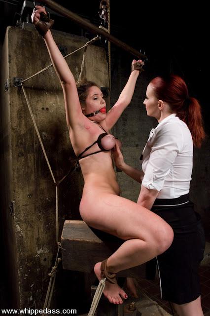 femme en prison nue pendant interrogatoire difficile , soumise à une dominatrice vicieuse.