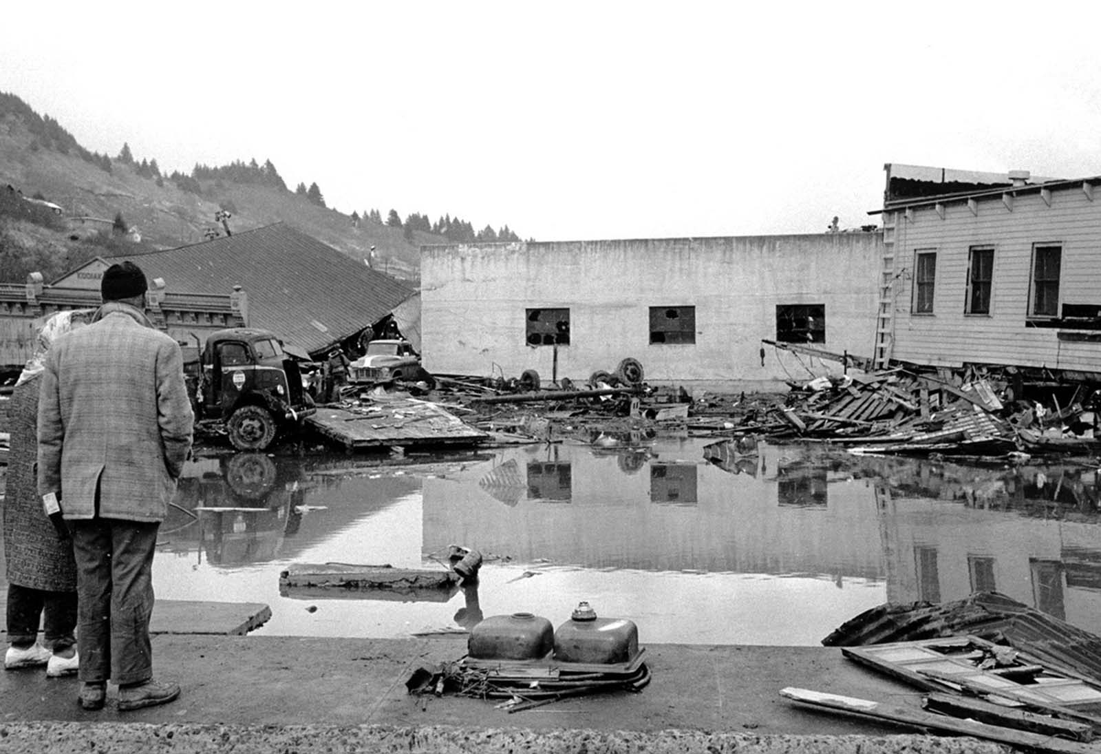 A forlorn couple stands on a concrete dock viewing the remains of the Kodiak waterfront on March 29, 1964.
