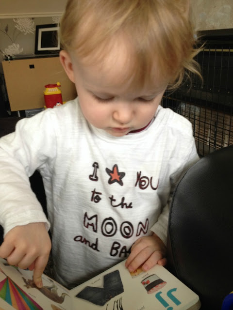 toddler pointing at picture in book and wearing t shirt that says I love you to the moon and back.