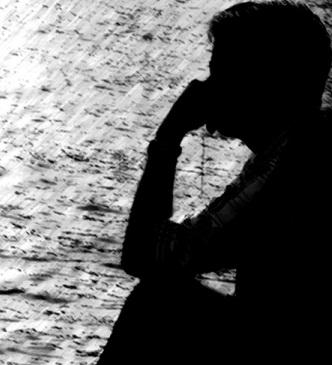 sombra de um homem sentado olhando o mar