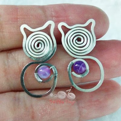 Close up of Wire wrapped cat earrings with Amethyst