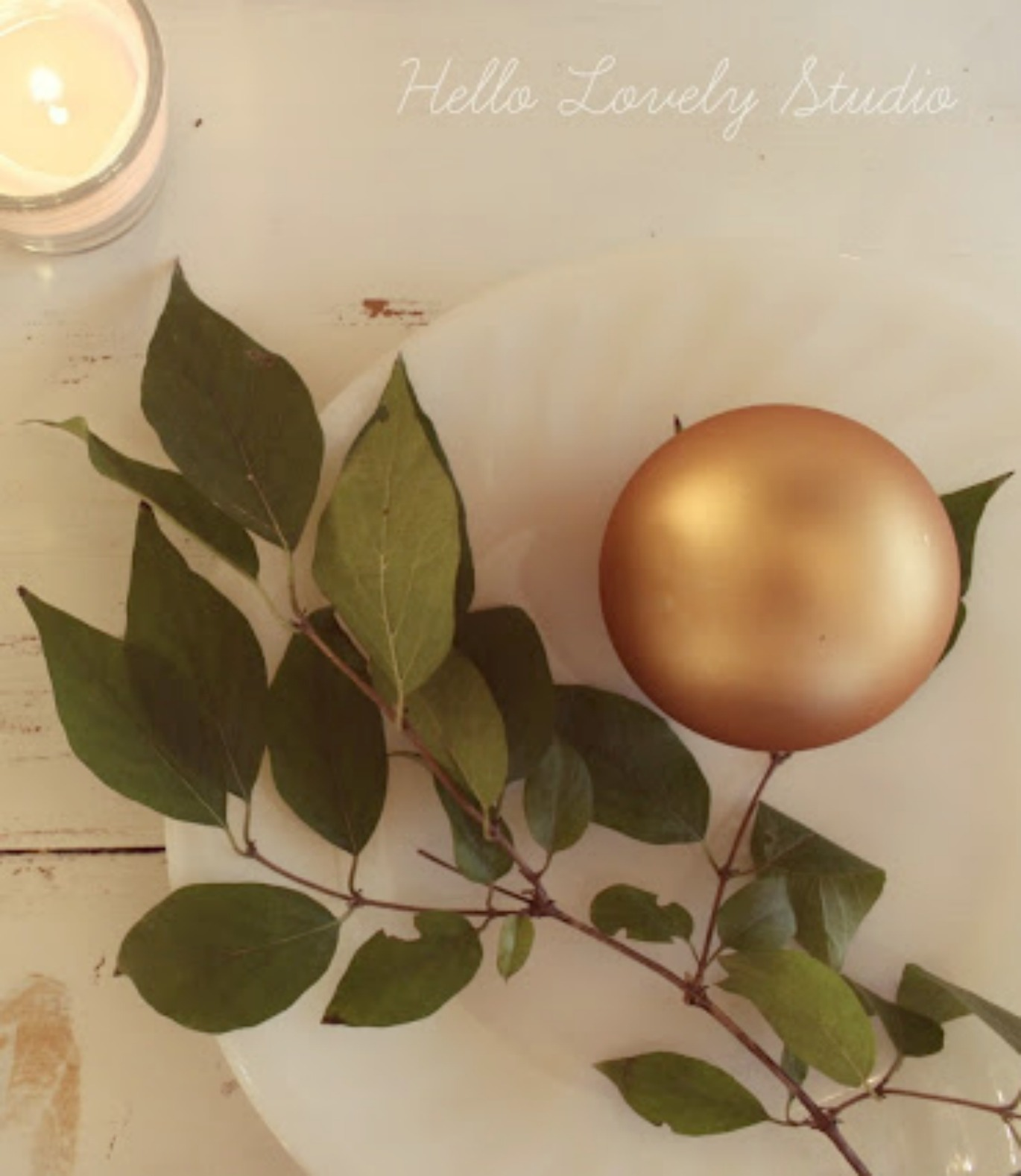 White farmhouse table with milkglass plate, fresh greenery, gold ball, and candle - Hello Lovely Studio