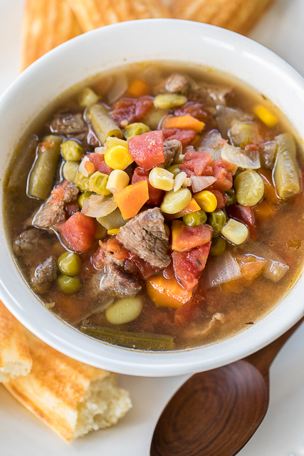 Slow Cooker Chunky Beef Vegetable Soup - seriously delicious! Stew meat, green beans, corn, lima beans, green peas, carrots, celery, onions and diced tomatoes slow cook all day long for an easy and delicious meal! Makes a ton! Freeze leftovers for later. Great for cool Fall and Winter nights! Everyone LOVES this easy slow cooker recipe.