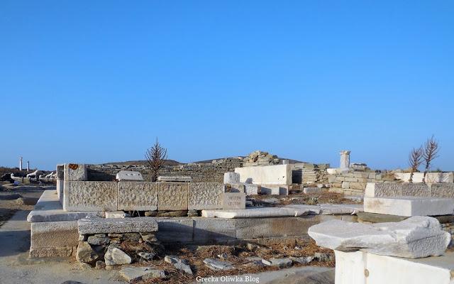 ruiny świątyni Leto na tle bezchmurnego greckiego nieba i spalonej słońcem trawy, biały marmur Grecja wyspa Delos
