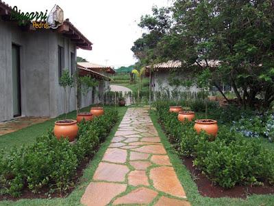 Execução do caminho no jardim com pedra Goiás tipo cacão assentado com juntas de grama com os canteiros de viburno e os vasos de barro com mudas de mexerica e o gramado com grama esmeralda em residência em Piracaia-SP.