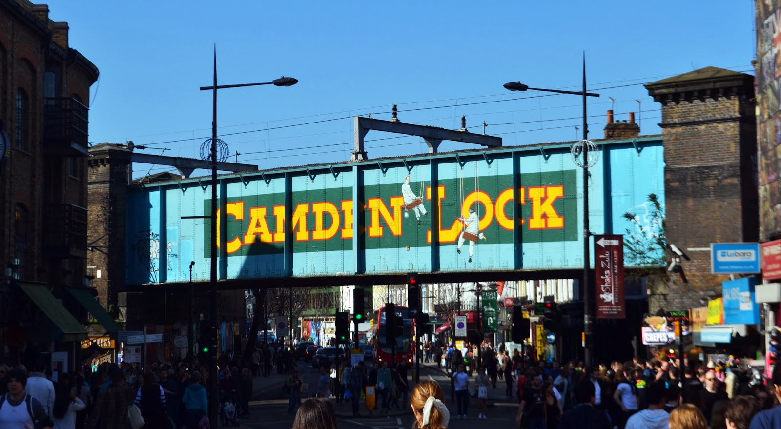 The main Camden Lock sign painting across a blue railway bridge