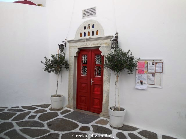 czerwone drzwi cerkwi obok donice z drzewkiem oliwnym