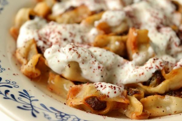 Bowl of Armenian dumplings with yogurt garlic sauce and sumac on top.