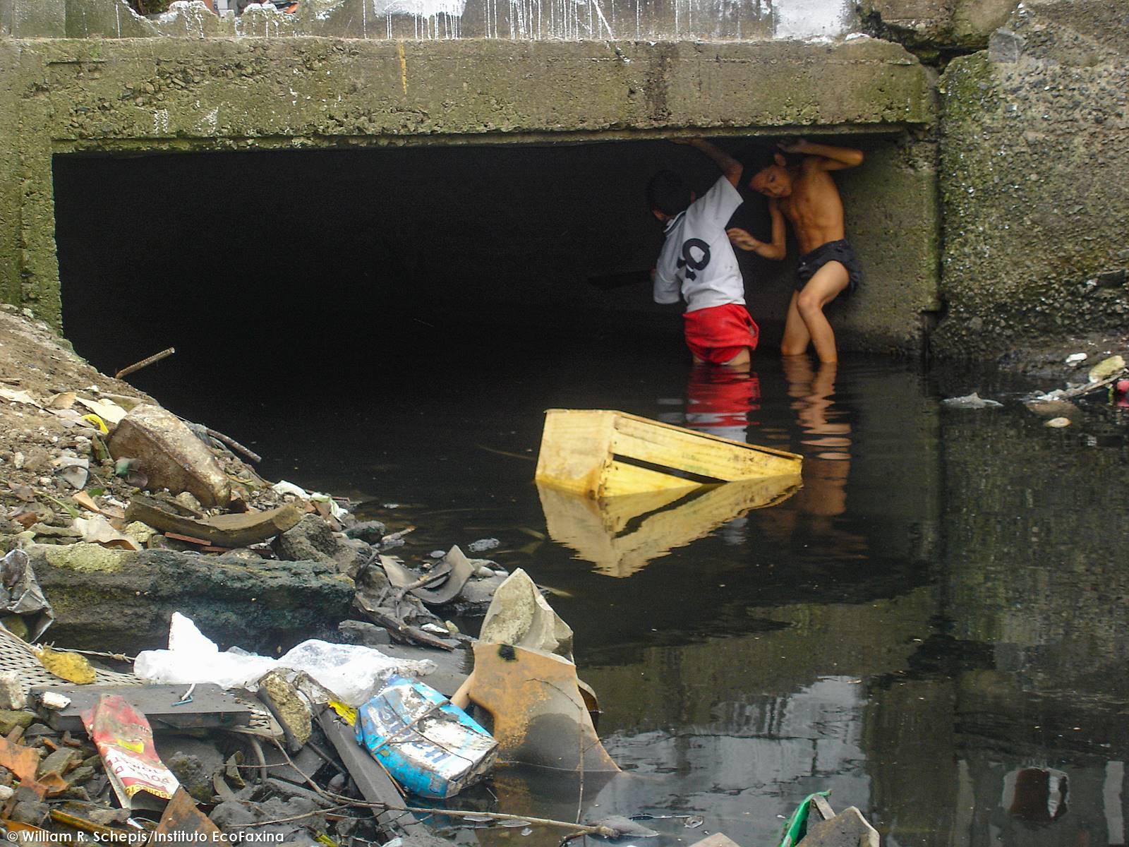 """O mangue poluído é a """"praia"""" da maioria das crianças que vivem em palafitas."""