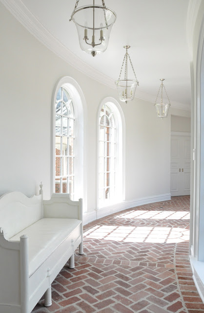 kathleen clements' curved hallway with arched windows, brick floor laid in a herringbone pattern, lanterns and white walls