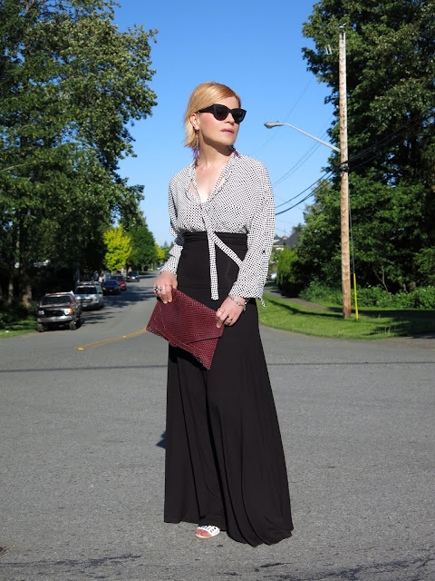 styling a black maxi skirt with a dotted blouse, cat-eye sunglasses, and reptile-embossed envelope clutch