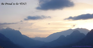 Image of a range of mountains as the sun rises with text: Be proud to be you!