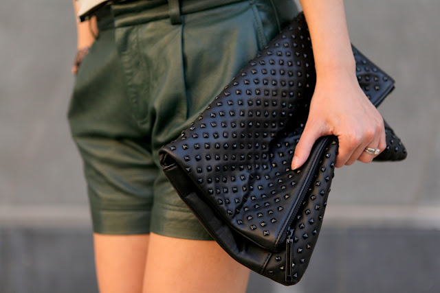 Green leather shorts and studded clutch