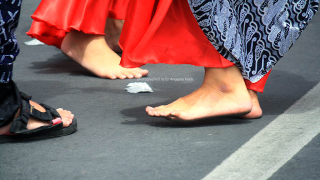 Penonton karnaval yang pakai sepatu, tetapi penari tetap tanpa alas kaki.
