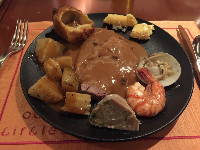 A plate of steak, vegetables, Yorkshire pudding, and gravy at Circles Event Cafe