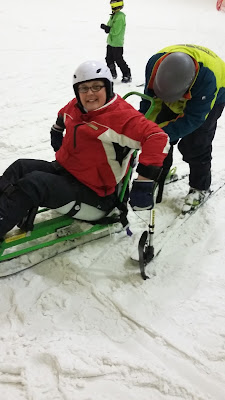 Picture of me in a sit-ski, holding myself up with outriggers.