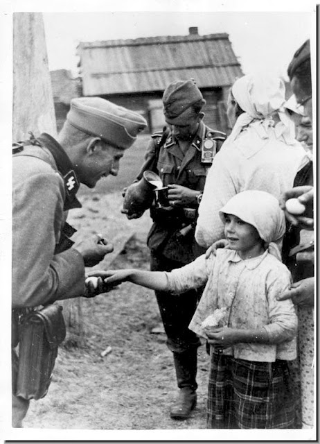 soldier socialises little  Russian girl offer food