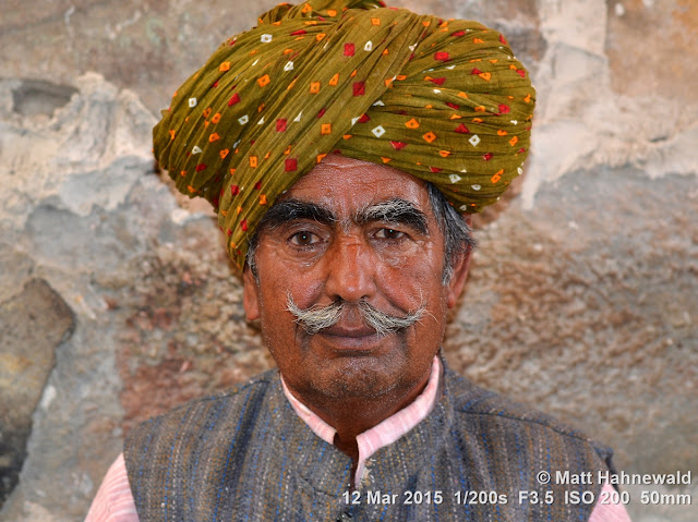 Rajasthani turban; pagari; moustache; Matt Hahnewald Photography; Facing the World; photography; photo; image; outstanding; fantastic; favourite; superior; excellent; inspirational; vibrant; breathtaking; Nikon D3100; Nikkor AF-S 50mm f/1.8G; prime lens; 50mm; 4 : 3 aspect ratio; horizontal format; closeup; portrait; portraiture; headshot; en face; front view; outdoor; colour; colourful; world cultures; cultural; character; personality; real people; human; human head; human face; human eyes; facial expression; eye contact; Rajasthani pagari; turban; consent; empathy; rapport; encounter; relationship; emotion; mood; environmental portrait; ethnic portrait; travel; travel portrait; travel destination; tradition; Jaisalmer; Rajasthan; India; one person; male; adult; Indian man; posing; authentic; incredible; awesome; Rajasthani man; street portrait