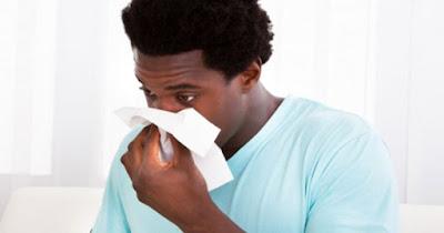 Black man sneezing because of spring allergies
