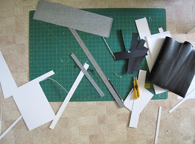 Large cutting board, ruler, stanley knife and various bits of card and paper on a kitchen floor.