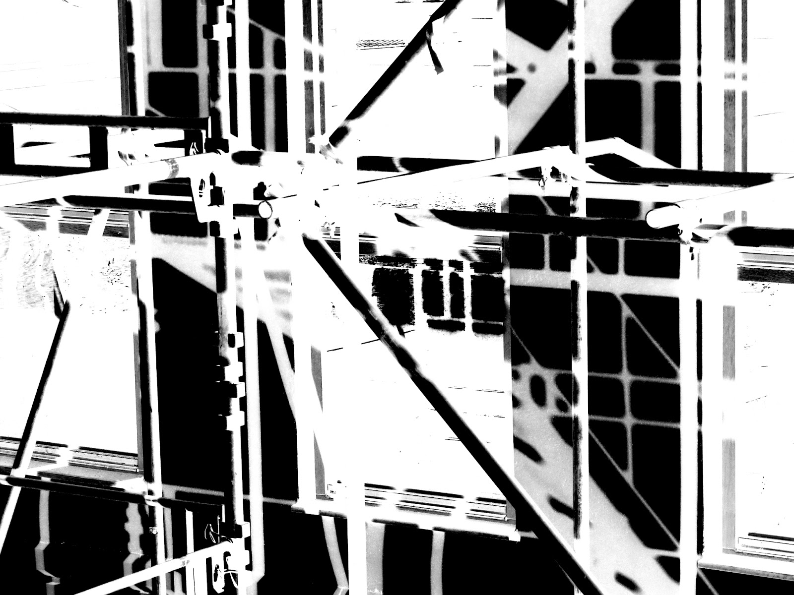 Scaffolding on building in black and white with colours inverted.