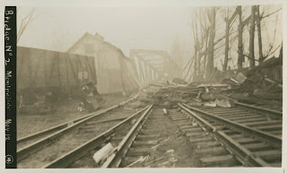 A black and white photograph of a damaged railroad, covered in debris.