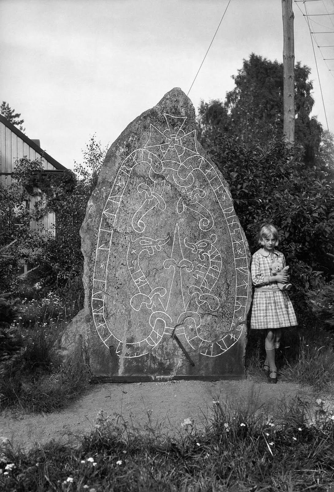 A girl with a teddy bear at a runestone in Söderby, Botkyrka. The inscription reads,