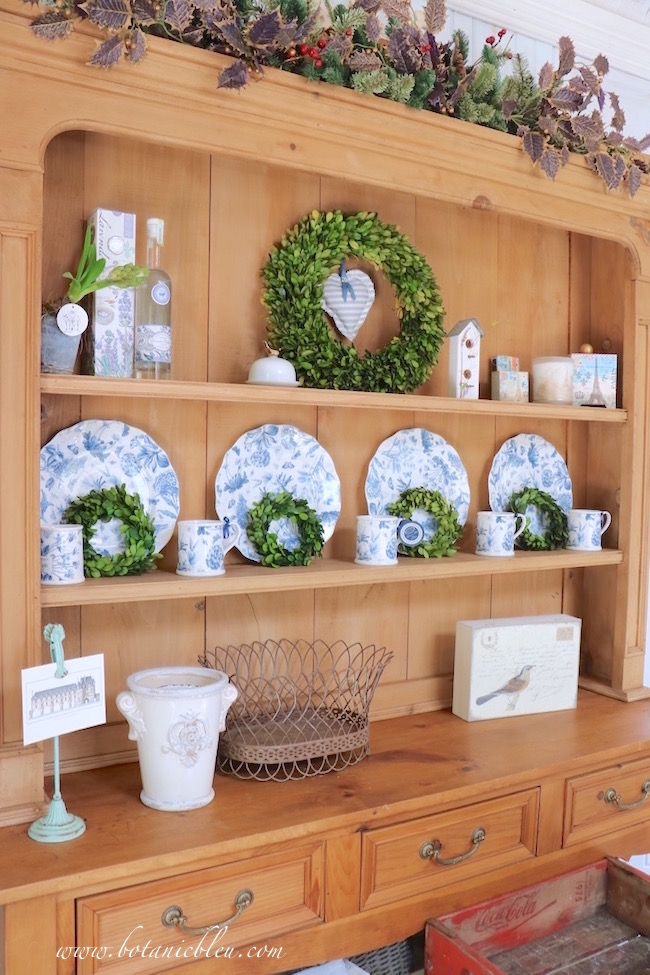garden-shed-vintage-pine-hutch-holds-blue-white-dishes-boxwood-wreaths