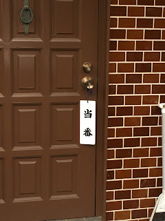 "A picture of a sign saying ""toban"" hanging  on the door of a member of the local neighbouhood association"