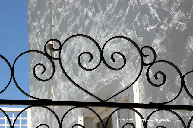 Ornaments over an entrance door of a white cubic house.