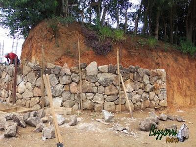 Execução do muro de pedra rústica sendo o tipo de pedra moledo na face do muro e no enchimento a pedra rachão. Muro de pedra com junta seca sem cimento nas juntas.