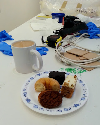 A mug of tea and a plate of cakes and biscuits on a table with tools for a gallery install, including rubber gloves, a tape measure, an extension cord and something wrapped in bubble wrap marked 'fragile'.