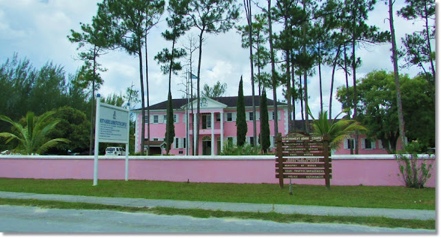 Two story government administration building painted hot pink.