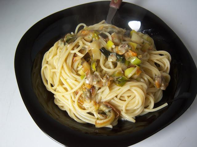 Fotografía de plato de espaguetis con salsa y berberechos.