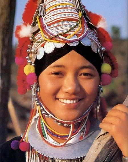 A young Akha lady poses for a photo in hilltop village outside of Chiang Mai, Thailand.