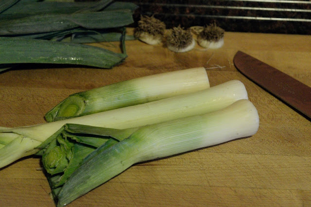 The leeks sitting on a cutting board.