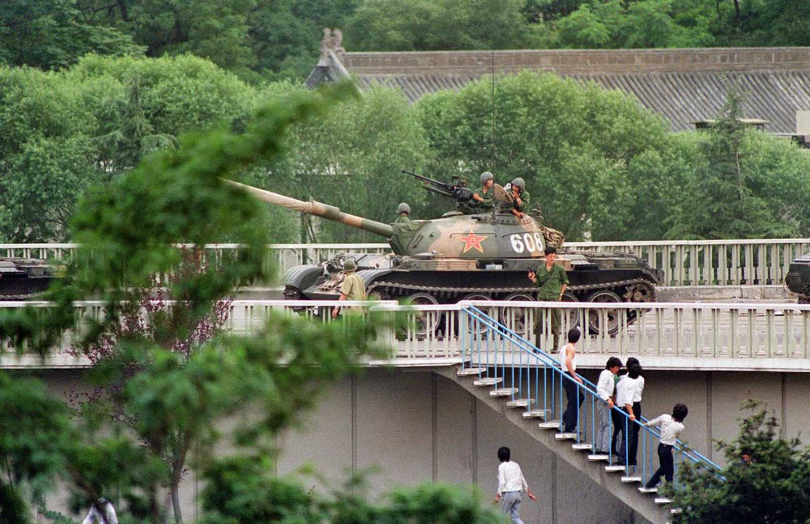 Chinese onlookers run away as a soldier threatens them with a gun on June 5, 1989 as tanks took position at Beijing's key intersections next to the diplomatic compound.