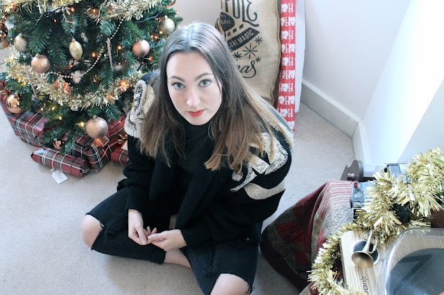 Fashion blogger wearing vintage cardigan next to a Christmas tree