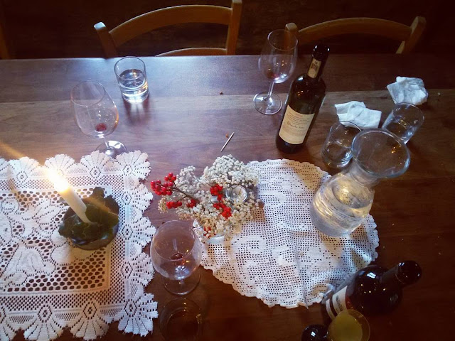 Empty bottles and wine glasses on a decorated table in the Chianti